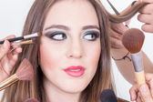 Closeup of beautiful blond girl getting hair and makeup done — Stock Photo