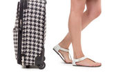 Suitcase and girls feet wearing sandals — Stock Photo