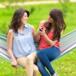 Two young girls resting on a hammock smiling — Stock Photo #50212357