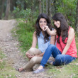 Two beautiful girls sitting in a forest — Stock Photo #50213299