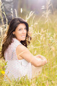 Beautiful young woman sitting on a wheat field — Stock Photo