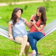 Two young girls resting on a hammock smiling — Stock Photo #50234503