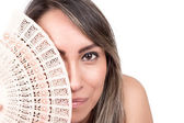 Young woman holding a fan in front of her face — Stock Photo
