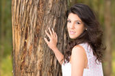 Gorgeous young girl posing besides a tree — Photo