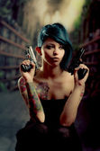 Provocative tattooed girl holding gun — Stock Photo