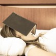 Young girl sleeping with book on her face — Stock Photo #50378563