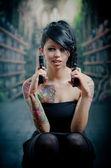 Provocative tattooed girl holding gun — Stock Photo