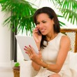 Beautiful young elegant woman holding digital tablet and talking on cell phone — Stock Photo #50380123