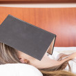 Young girl sleeping with book on her face — Stock Photo #50439521