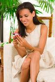 Beautiful young elegant woman sitting in livingroom — Stock Photo