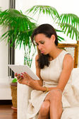 Beautiful young elegant woman holding a digital tablet sitting on sofa — Stock Photo