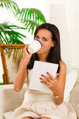 Beautiful young elegant woman sitting in sofa using tablet and drinking a coffee — Stock Photo