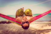 Beautiful young girl lying in a hammock holding two coconuts — Stok fotoğraf