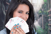 Beautiful young girl holding deck of cards — Stock Photo