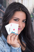 Beautiful young girl holding deck of cards — Photo