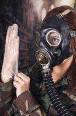 Young girl wearing military uniform and gas mask over dark background — Stock Photo