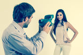 Handsome young man taking photos of beautiful girl with instant camera — Stock Photo
