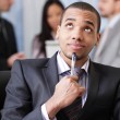 Pensive african-american business man with his coworkers on the background — Stock Photo