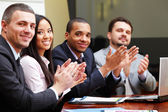 Multi ethnic business group greets you with clapping — Stock Photo