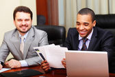 Two businesspartners joking while working with documents — Stock Photo