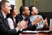 Multi ethnic business group greets somebody — Stock Photo