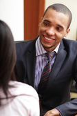 Young african-american businessman having a conversation with her coworker — Stock Photo