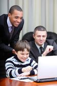 Kid boy explains multi ethnic business team how to work — Stock Photo