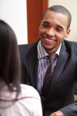 Young african-american businessman having a conversation with his female coworker — Stock Photo