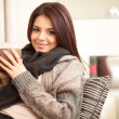 Happy young woman sitting on sofa in cosy cloths with cup of cof — Stock Photo