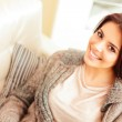 Portrait of a young beautiful woman on sofa — Stock Photo #25729713