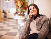 Young happy woman sitting on the sofa at home while talking on p — Stok fotoğraf