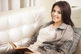 Portrait of a young beautiful woman on sofa — Stock Photo