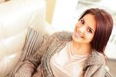 Portrait of a young beautiful woman on sofa — Zdjęcie stockowe