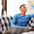 Handsome young man using laptop at home — Stock Photo