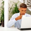 Mature happy businessman working with laptop — Stock Photo