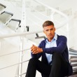 Mature pensive man sitting on stairs — Stock Photo #30023547