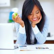 Young happy asian woman reading newspaper and eating apple — Stock Photo #30023645