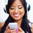 Stock Photo: Young asian woman in headphones listening to music