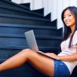 Young beautiful asian woman using laptop on stairs — Stock Photo #30023765