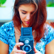 Young beautiful woman making a shot with a retro camera — Stock Photo #30024255