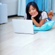 Young beautiful asian woman sitting on the floor with laptop — Stock Photo #30024273