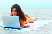Beautiful woman in swimming suit using her tablet on the beach — Stock Photo