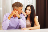 Happy beautiful couple sitting at the table at home — Stock Photo
