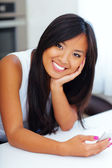 Young happy asian woman at home with her smartphone — Stock Photo