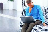 Mladý muž pracuje na notebooku doma absorbované — Stock fotografie