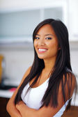 Young happy asian woman with arms folded at home — Stock Photo