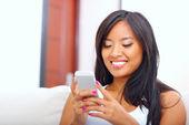 Texto de jovem mulher asiática de mensagens com seu smartphone — Fotografia Stock