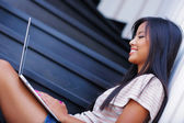 Young beautiful asian woman using laptop on stairs at home — Stock Photo