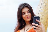 Mulher jovem feliz usando seu smartphone na praia — Fotografia Stock