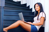 Young beautiful asian woman using laptop on stairs — Stock Photo